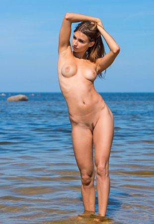bare breasts: Beautiful young naked woman posing on the beach. Enjoying summer time near the sea