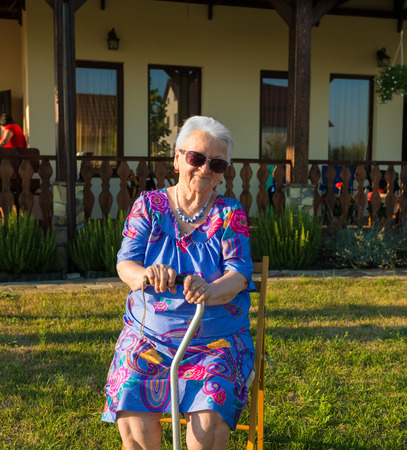 cane chair: Old woman sitting on a chair with a cane in the garden