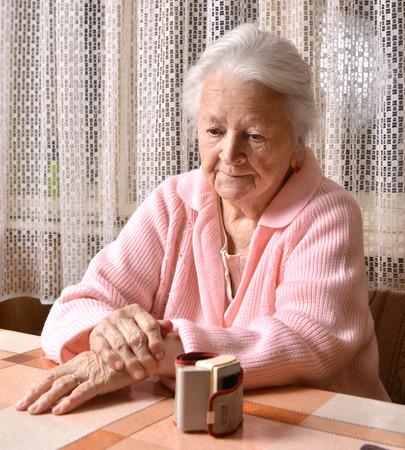 sad old woman: Mujer mayor triste y la medici�n de la presi�n arterial Foto de archivo