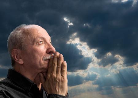 arrepentimiento: Hombre mayor que ruega agaist cielo nublado azul