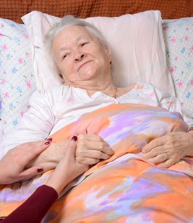 Caring hands holding old ladys hands in bed at hospital photo