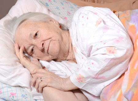 Sick old woman lying at bed Standard-Bild