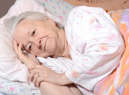 Zieke oude vrouw liggend op bed Stockfoto