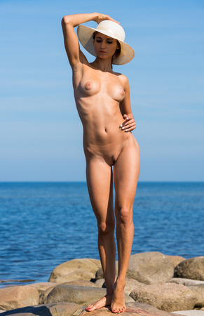 wet breast: Young beautiful nude woman with a white hat posing on the beach. Enjoying summer time near the sea