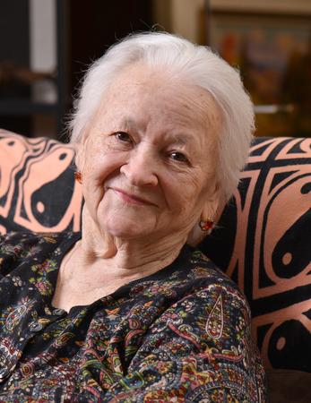 Portret van glimlachende oude vrouw thuis Stockfoto