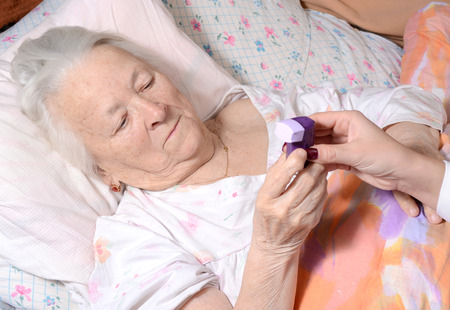 Female doctor giving asthma inhaler to old woman