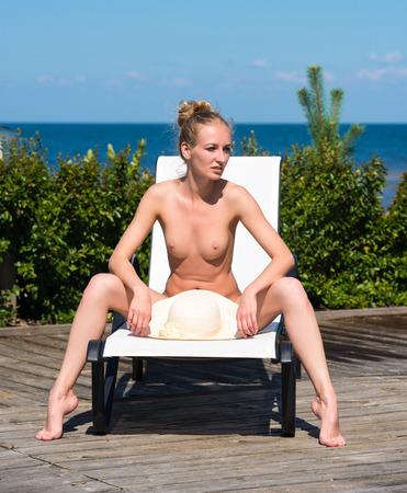 wet breast: Beautiful naked woman sunbathing on sunbed near swimming pool