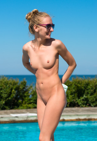 Beautiful young naked woman enjoying summer time near the  swimming pool Stock Photo