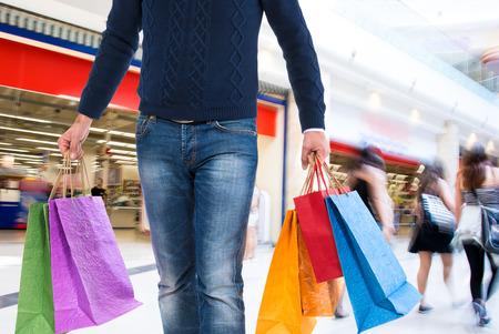 centro comercial: Hombre con bolsas de la compra en un centro comercial