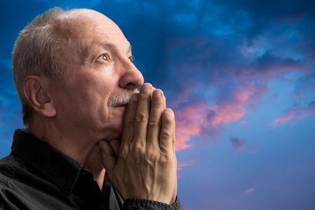 hombre orando: Hombre mayor que ruega agaist cielo nublado azul