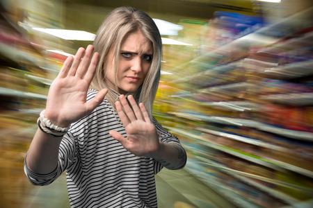 gestos: Mujer joven que gesticula la parada en el centro comercial