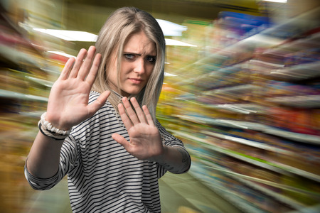 gestures: Young woman gesturing stop in the shopping mall
