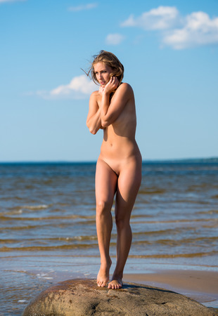 female nudity: Young beautiful naked woman posing on stones near the sea. Enjoying summer time