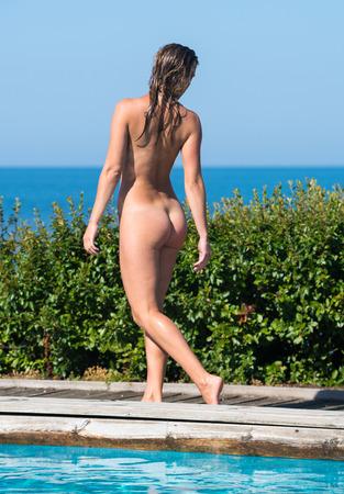 Beautiful young naked woman enjoying summertime near the  swimming pool