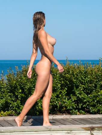 wet breast: Beautiful young naked woman enjoying summertime near the  swimming pool