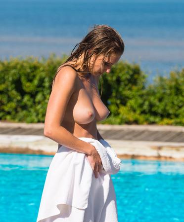 Beautiful young naked woman posing near the  swimming pool Stock Photo