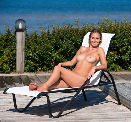 Beautiful naked woman sunbathing on sunbed. Enjoying summer time Stock Photo