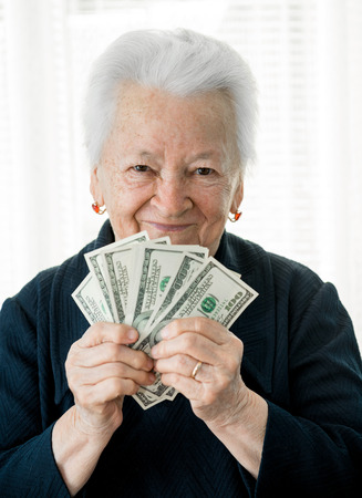 woman holding money: Smiling old woman holding money in hands on a white background Stock Photo