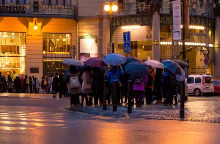 zebra crossing: PRAGUE, CZECH REPUBLIC - 03 January 2015: Crowd of people under umbrellas on zebra crossing in Prague, Czech republic