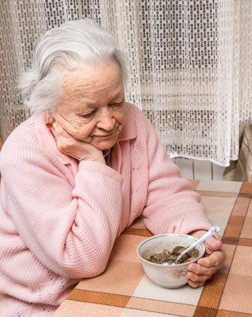 Oude trieste vrouw die het eten thuis Stockfoto