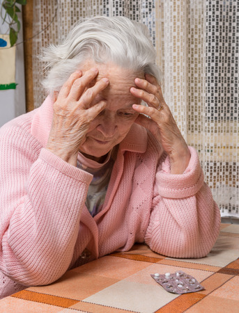 too many: Old sad woman with pills at home.  Worried about  having to take too many pills