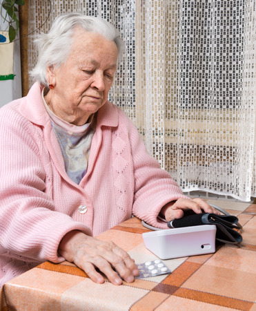 Old  retired woman taking blood pressure at home