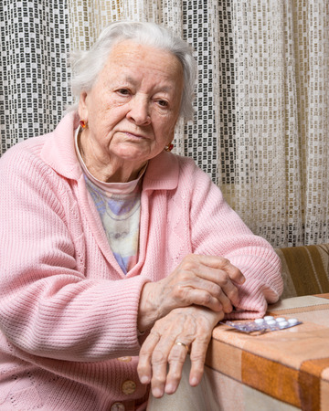Old sad woman with pills at home.  Worried about  having to take too many pills