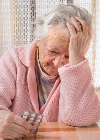 medicalcare: Old sad woman holding pills at home