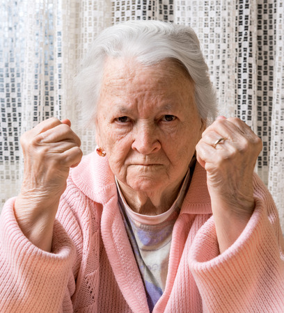 Angry old woman making fists at home