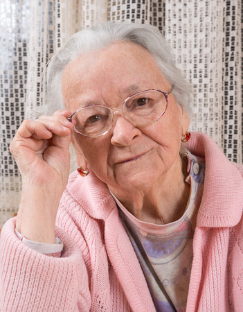 saddened: Portrait of old sad woman in glasses at home