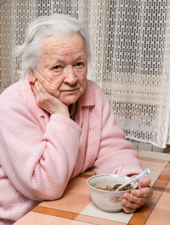 Old sad woman eating at home