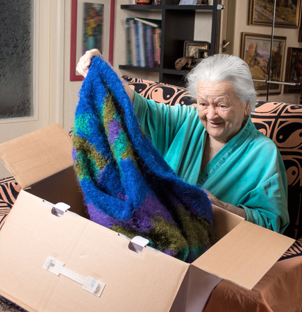 Old woman getting out a present from a large cardboard box Фото со стока