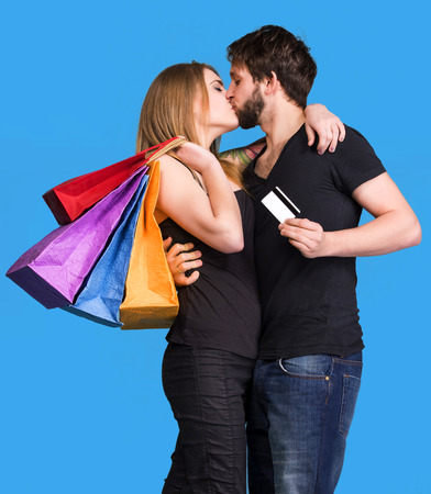 Happy kissing couple with shopping bags on a blue background. Man holding credit card photo