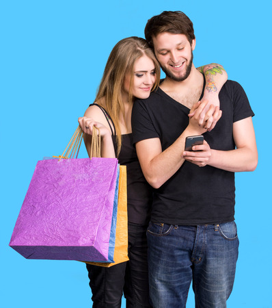 Happy young couple with shopping bags looking at mobile phone on a blue background