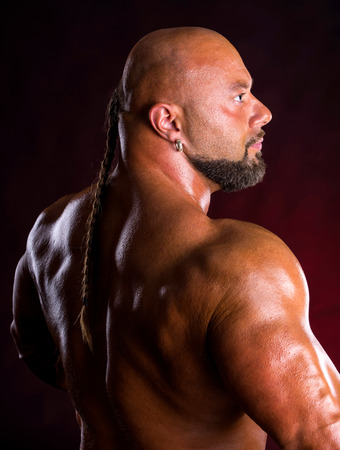 dorsi: Athlete bodybuilder  demonstrating muscles of the back and arms on a dark red background Stock Photo