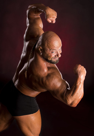 dorsi: Athlete bodybuilder demonstrating muscles of the back and arms on a dark red background