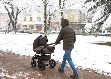 Father with a small childin the stroller walking down the street. Intentional motion blur