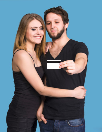 Happy couple on a blue . Man holding credit card photo