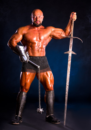 Handsome muscular ancient warrior with a sword and mace on a dark smoky background