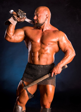 medieval warrior: Handsome muscular ancient warrior with a sword and axe on a dark smoky background Stock Photo