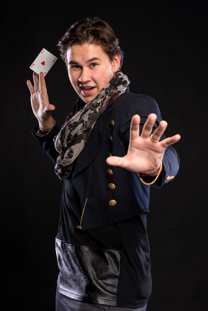 ace: Young magician showing ace on a black background Stock Photo