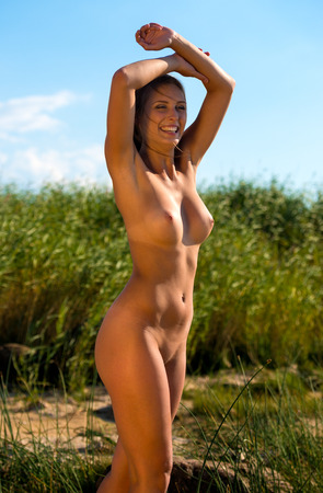 Young beautiful nude woman posing on nature background Stock Photo