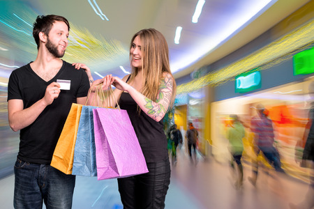 Happy couple with shopping bags in the mall. Man holding credit card photo