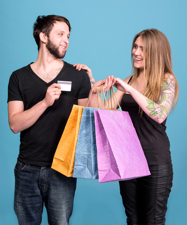 Happy couple with shopping bags on a blue background. Man holding credit card photo
