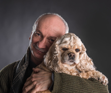 Happy old man with a dog on a dark background 免版税图像