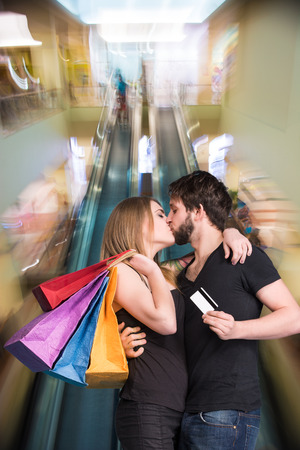 Happy kissing couple with shopping bags in the mall. Man holding credit card photo