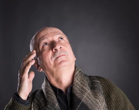 Portrait of thoughtful senior man on a dark background