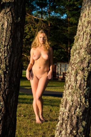 nude nature: Beautiful young nude woman posing outdoor. Enjoying summer time