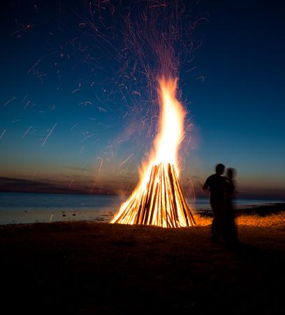 火災の背景に愛のカップルのシルエットです。ビーチでのロマンチックな夜