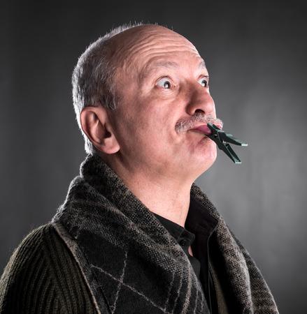 Senior man die stilte houdt met gesloten mond door wasknijper op een donkere achtergrond